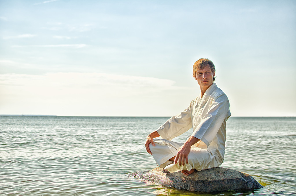 Man in kimono meditating on the rock in the sea